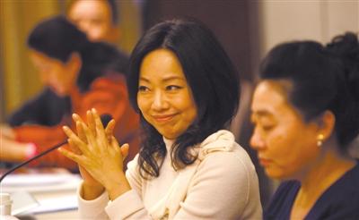 政协委员陈宁宁听到其他委员发言后双手交错,露出会心的微...