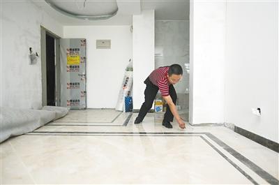 工作人员正在检查地面地砖铺贴是否合格.图片