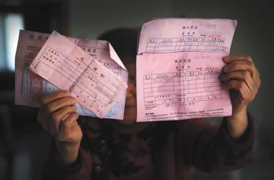 2月24日,房山某小区,85岁的杨慧(化名)拿着几张买收藏品时的收据和购买凭证。