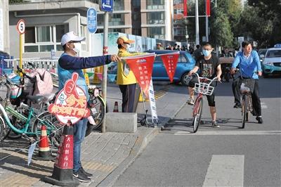 文明引導見成效 騎手主動推車過馬路